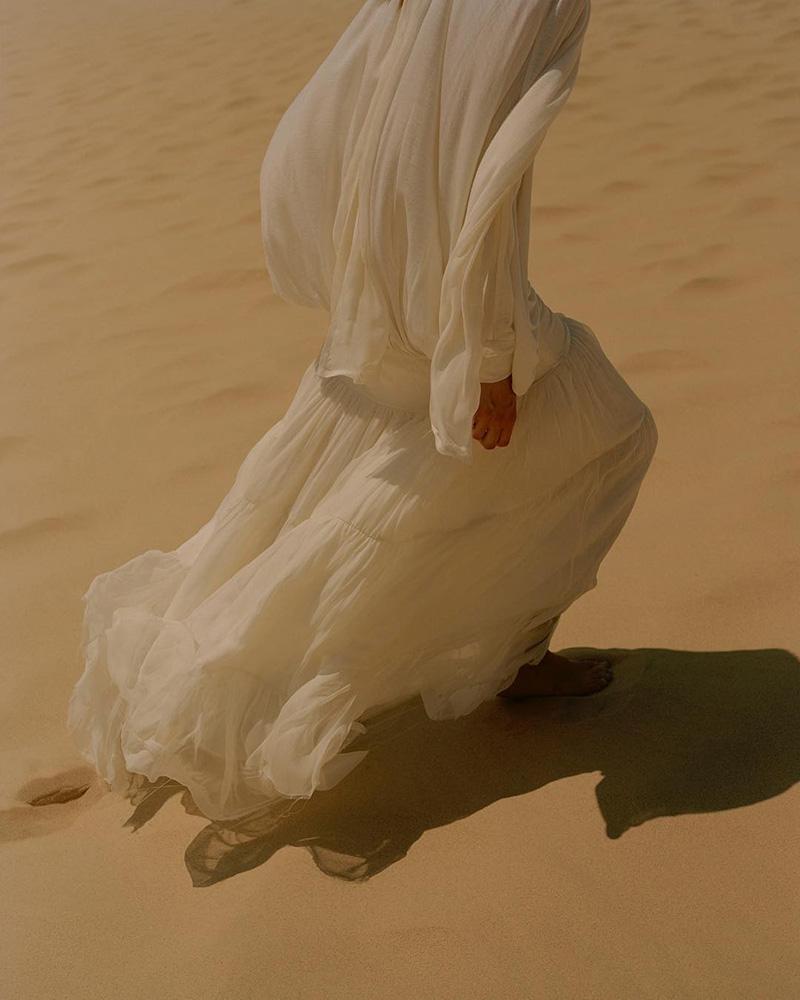 Фигура, идущей по песку пустыни женщины в белых одеждах - лучшая иллюстрация энергетической гармонии человека с окружающим миром